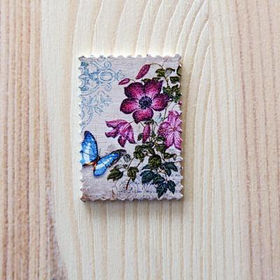 Bélyeg, lila virág, poly. Mérete: 25x40x2 mm